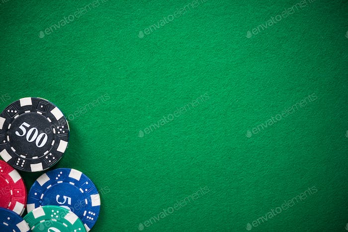 Casino chips on green empty cloth, spotlight background