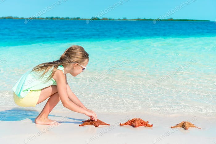 Adorable little girl take care of red starfish on white empty beach
