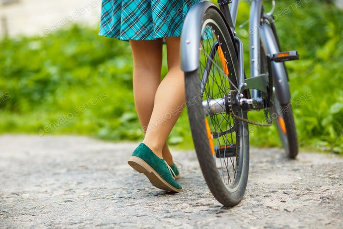 Legs of a woman in shoes with a bicycle