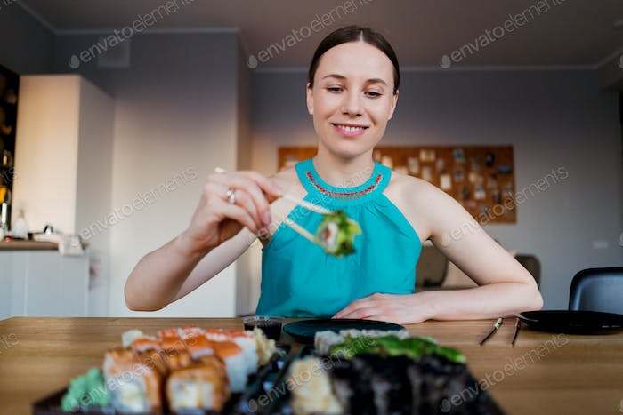 Happy woman eating delicious sushi