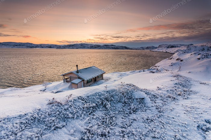 Cottage on the shore of the Arctic Ocean at sunset in winter
