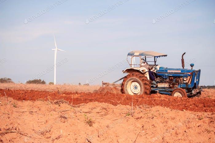 Landwirte verwenden Traktoren, um den Boden zu pflügen