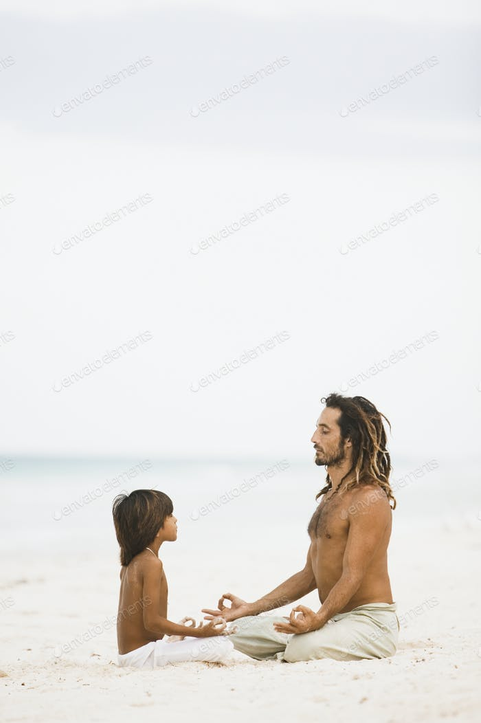 Father and son meditating on the beach