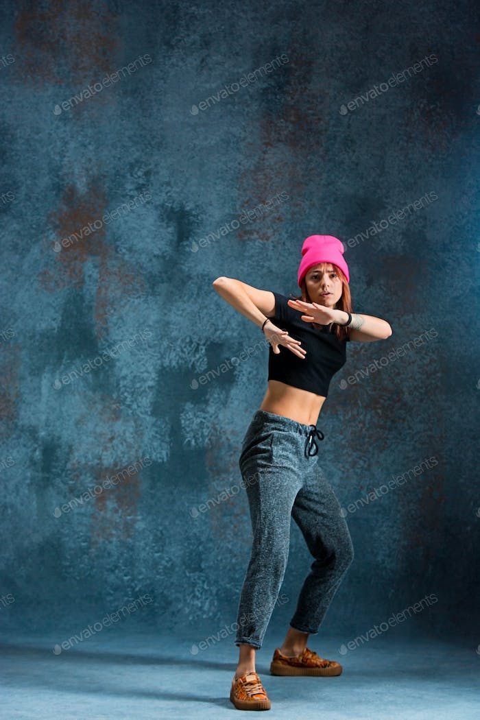 Young girl break dancing on wall background.