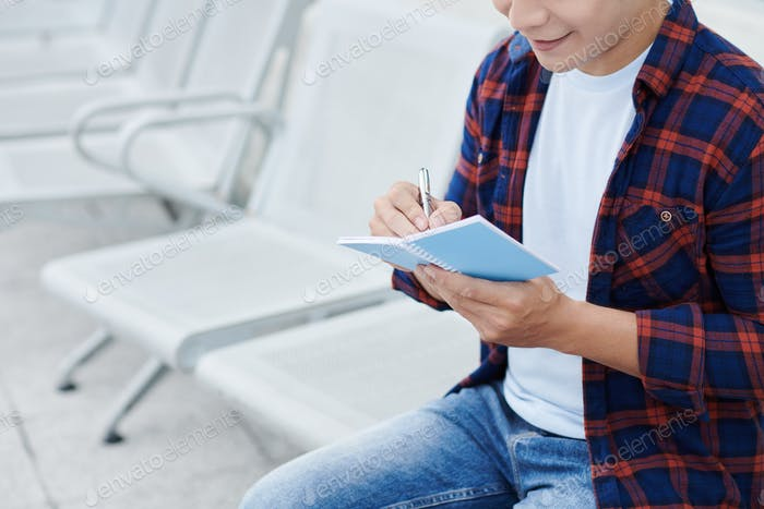 Man in Casual Shirt Making Notes