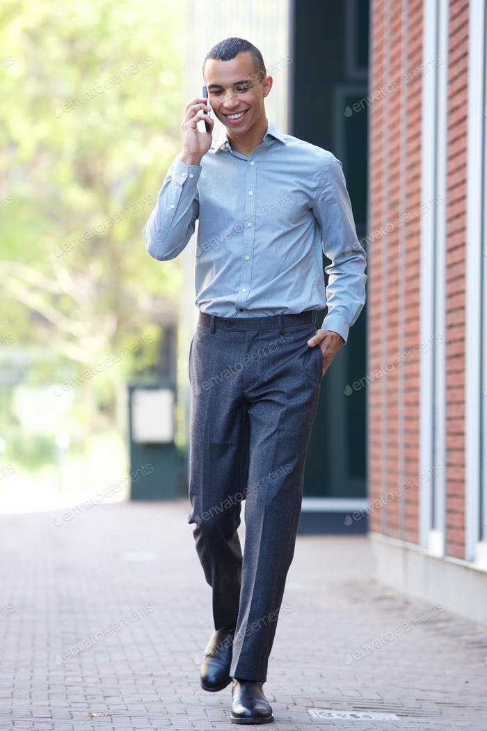 young businessman walking and talking with cellphone