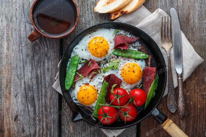 Fried eggs in a frying pan with cherry tomatoes, green peas and pastrami. Copyspace