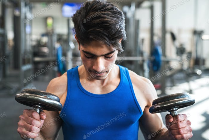 Young fit hispanic man in gym exercising with dumbbells.