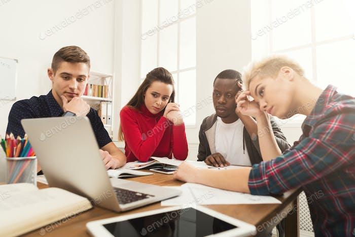 Multiethnische Klassenkameraden bereiten sich auf die Prüfung zusammen vor