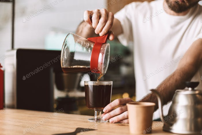 Close up photo of barista at counter in cafe pouring filter coffee in glass