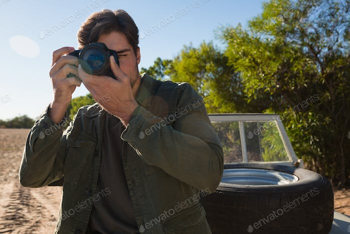 Young man photographing by vehicle