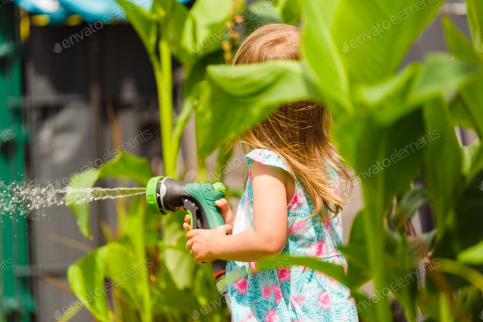 2-3 year old girl with garden hose water the plants plants