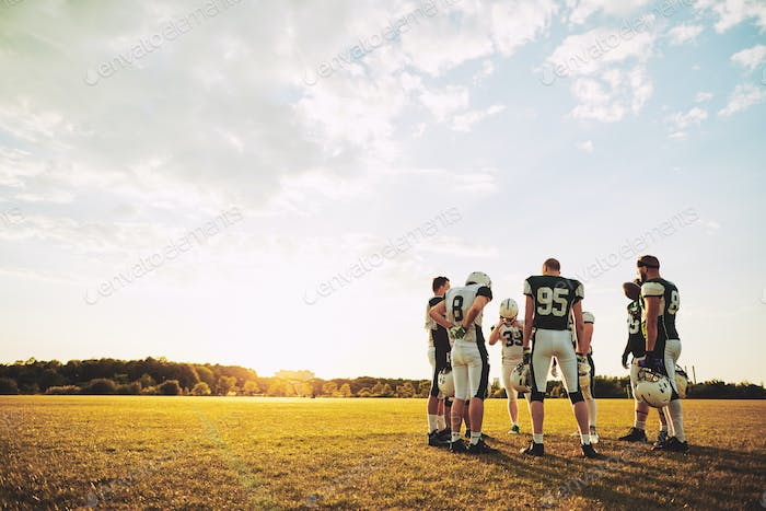 American football players talking game strategy during an afternoon practice