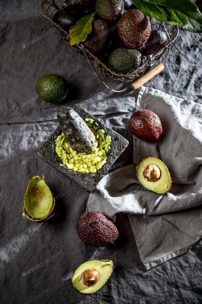 Mexican guacamole sauce in stone mortar, full basket with avocado, half of avocado