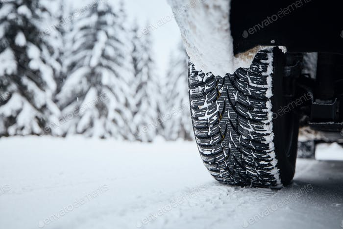 Tire of car on snow covered and icy road