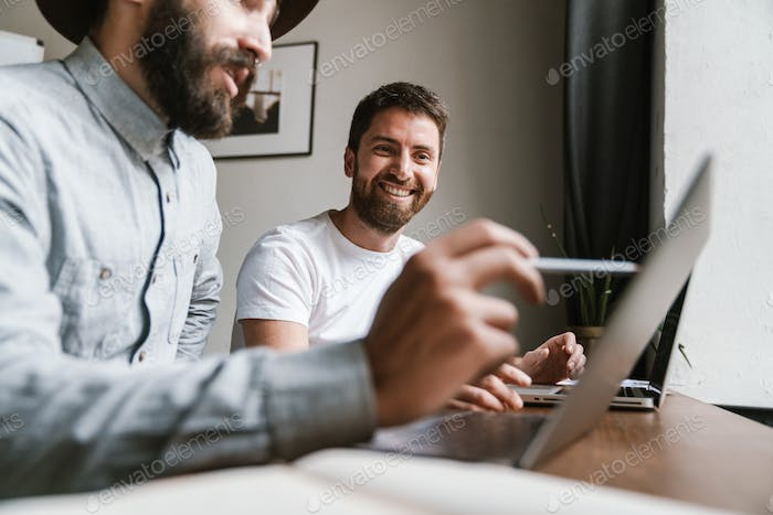 Image of caucasian young businesslike men working together at office