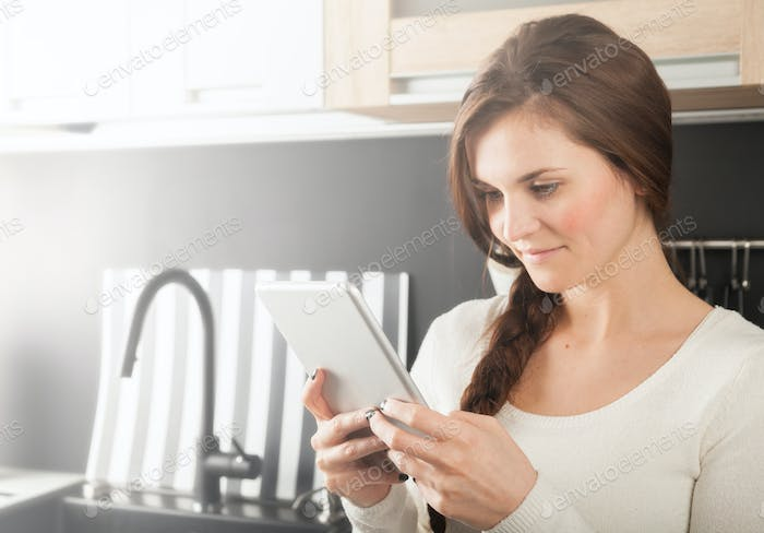 Woman using tablet to cook in home kitchen