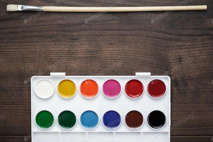 Box von Farben und ein Pinsel auf dem Tisch