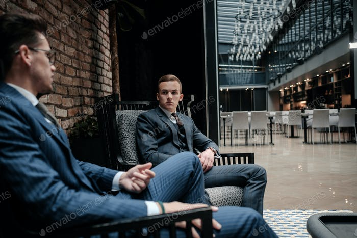 два молодого джентльмена имея разговор