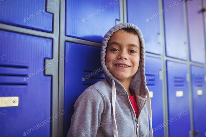Portrait of smiling boy standing by lockers