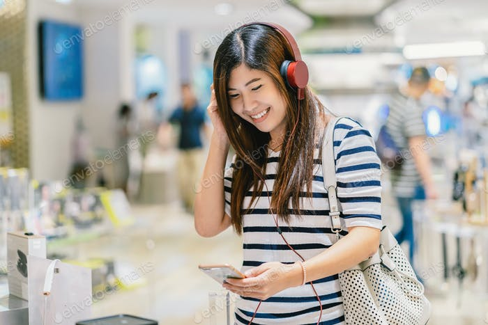 Happy Asian woman listening and testing technology Earphone or headphones