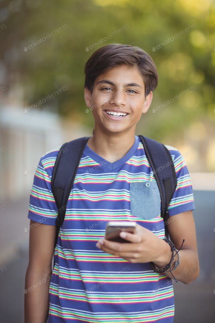 Schoolboy using mobile phone in campus at school