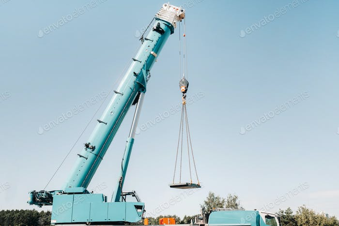 the stove is loaded onto a large blue car crane and prepared for operation . The largest truck crane