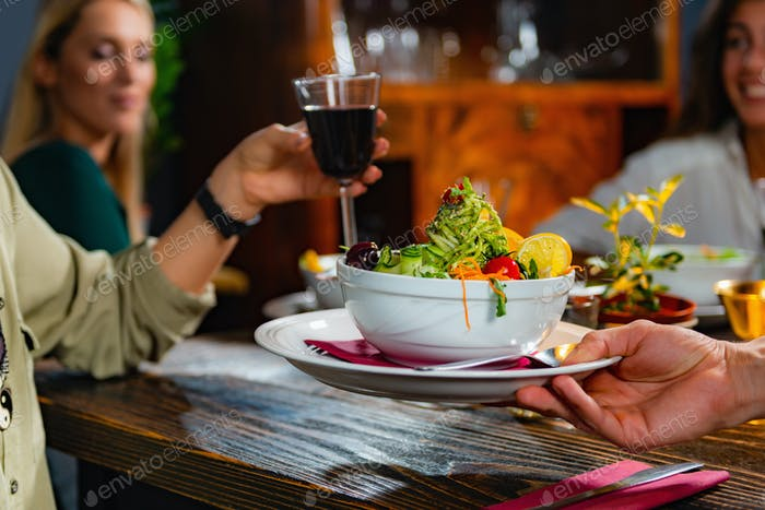 Waiter bringing a plate with vegetarian meal.