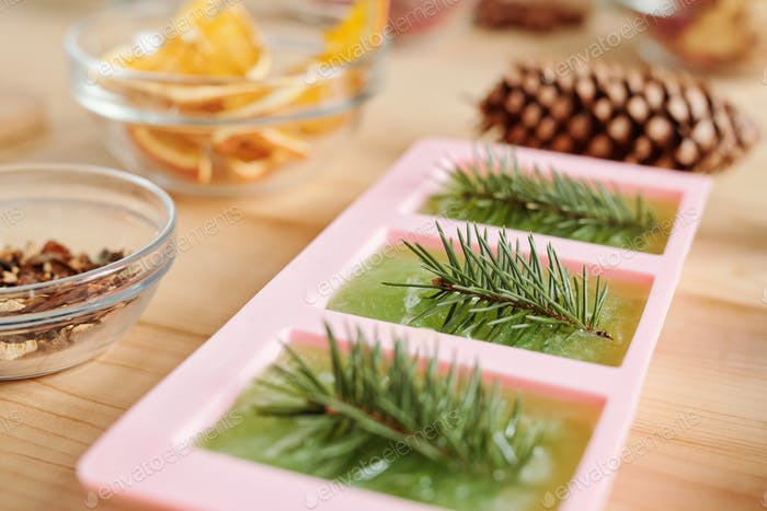Handmade green soap with conifer and glassware with aromatic ingredients