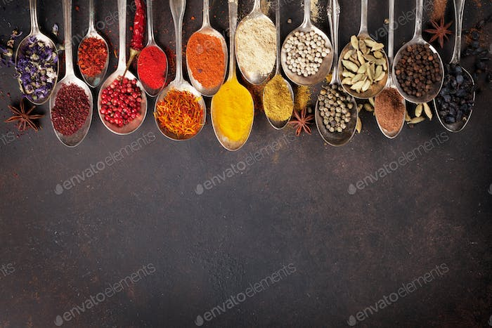 Various spices spoons on stone table. Top view