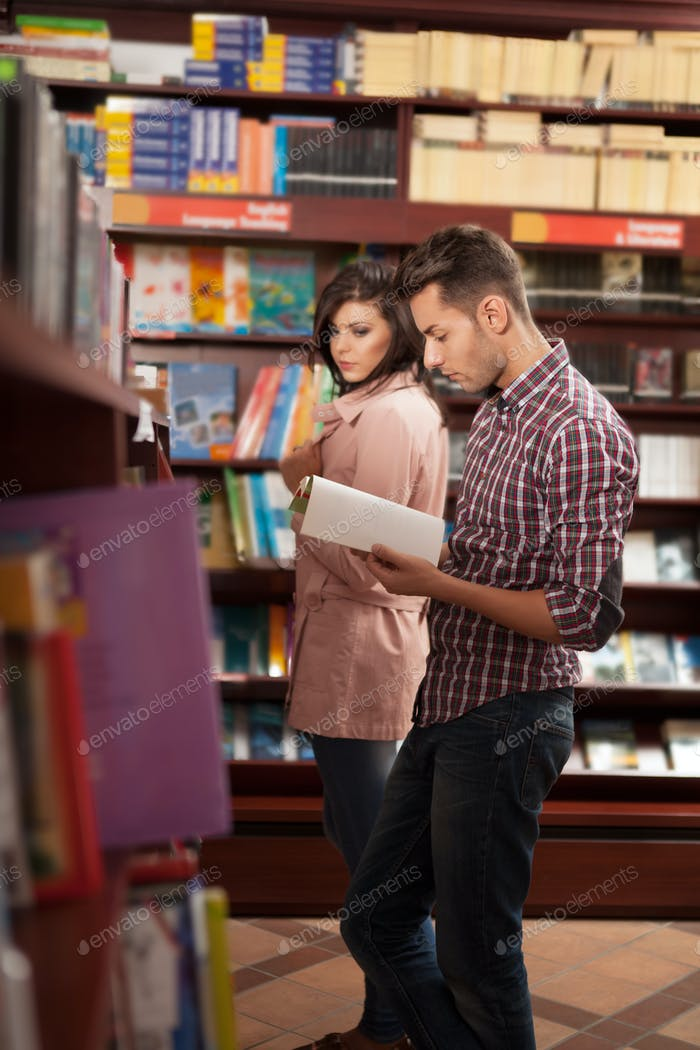 young guy reading in bookstore