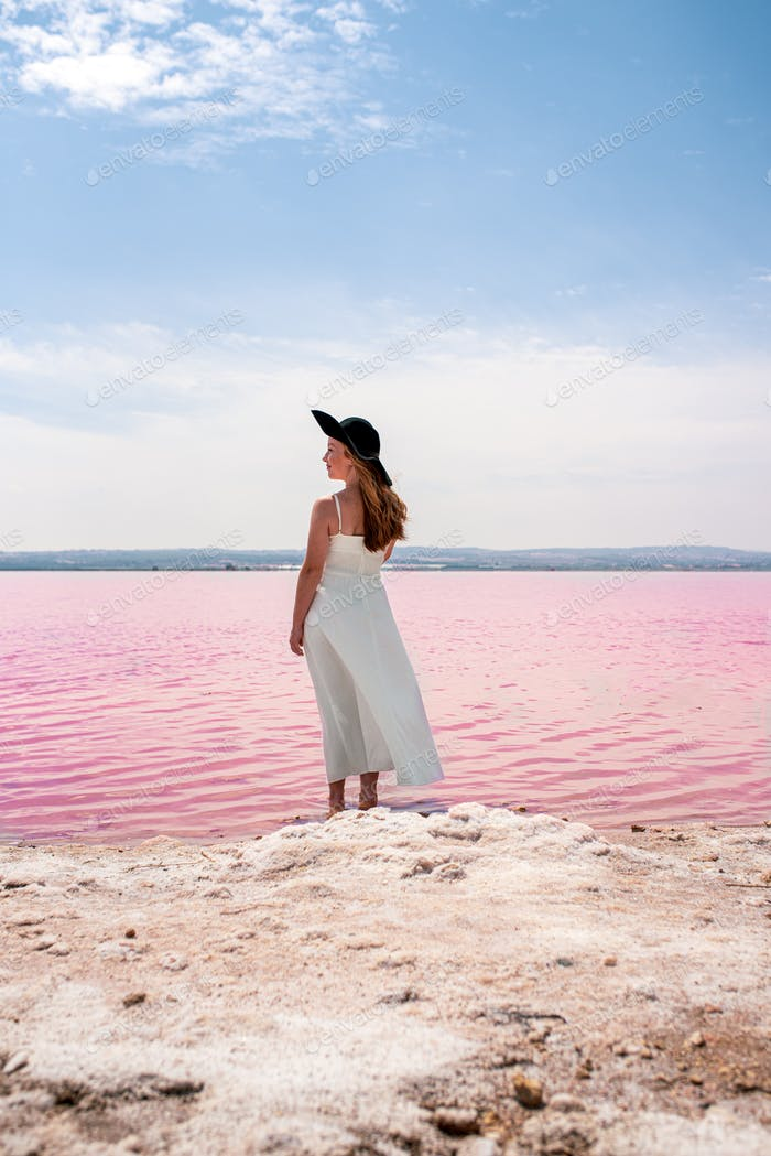 Back view of cute teenager woman wearing white dress walking on a amazing pink lake