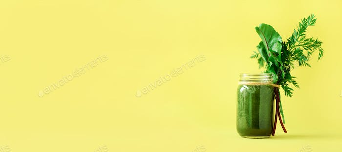 Banner of smoothie with beet greens and carrot tops on yellow background, copy space. Summer vegan