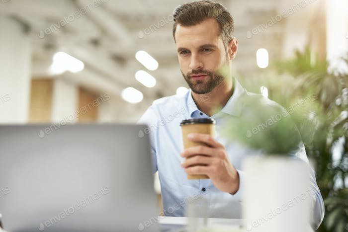 Enjoying morning coffee at work and checking e-mail