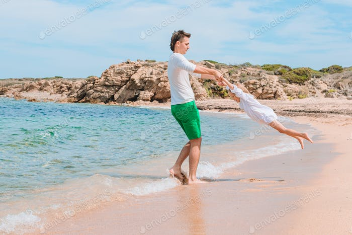 Kleines Mädchen und glückliche Papa mit Spaß während Strandurlaub
