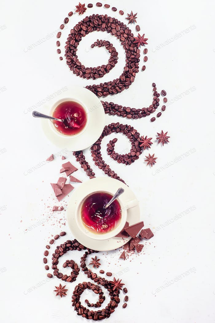 Coffee grains lying in the shape of a swirl with the cup, cinnamon, anise stars and chocolate