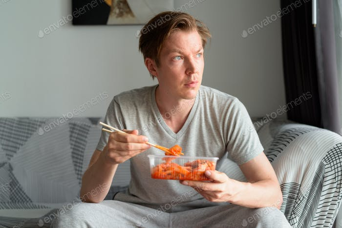 Young handsome man eating kimchi and thinking in the living room at home