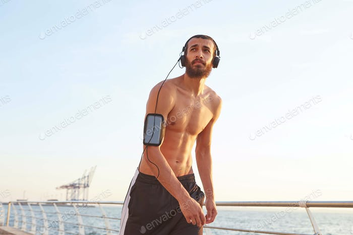 Young athletic bearded man after extreme sport walking at the seaside, looking away