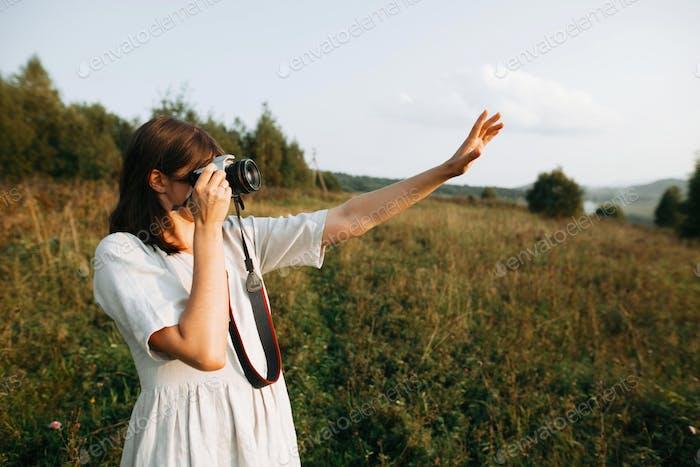 Stylish boho girl taking photo on film analog photo camera of grass and wildflowers