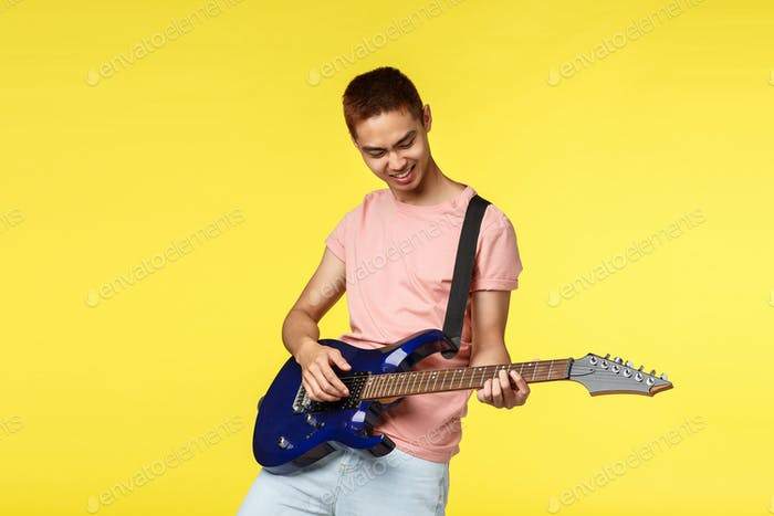 Lifestyle, leisure and youth concept. Portrait of happy, cool and stylish asian guy playing in band