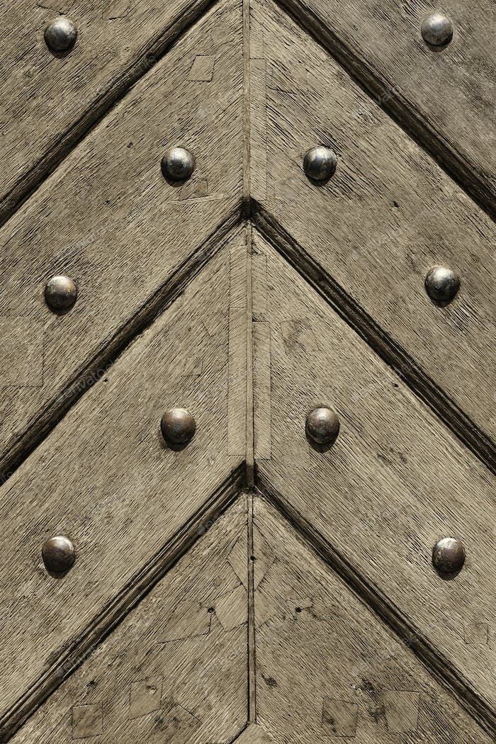 Fragment of old wooden doors with metal rivets
