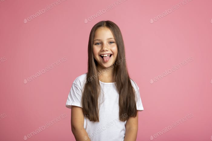 Happy child. Cheerful little kid showing tongue, on pink background