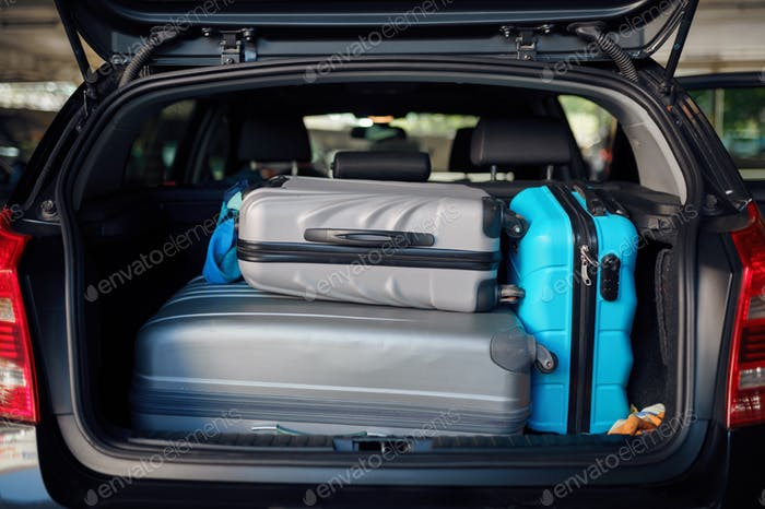 Suitcases in opened car trunk on parking, nobody