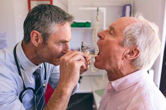 Male doctor checking senior male patient mouth with otoscope at clinic at retirement