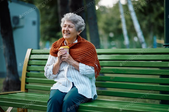 Dranny in scarf drinks hot coffee on the bench