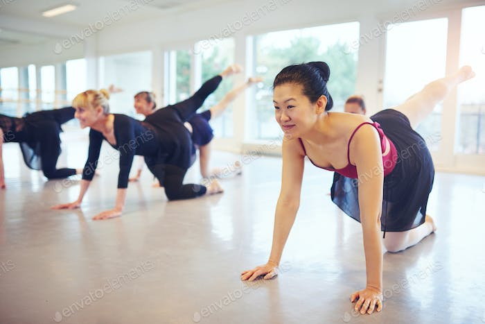 Multiethnic ballet group doing exercises on floor