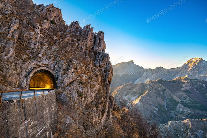 Alpi Apuane mountain road pass and tunnel view at sunset. Carrar