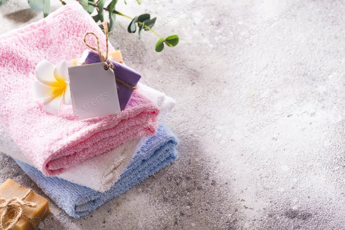 Spa set from fresh natural bath towels with handmade soap and flower on a light grey background