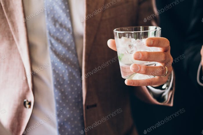 hands of stylish people cheering with glasses of whiskey