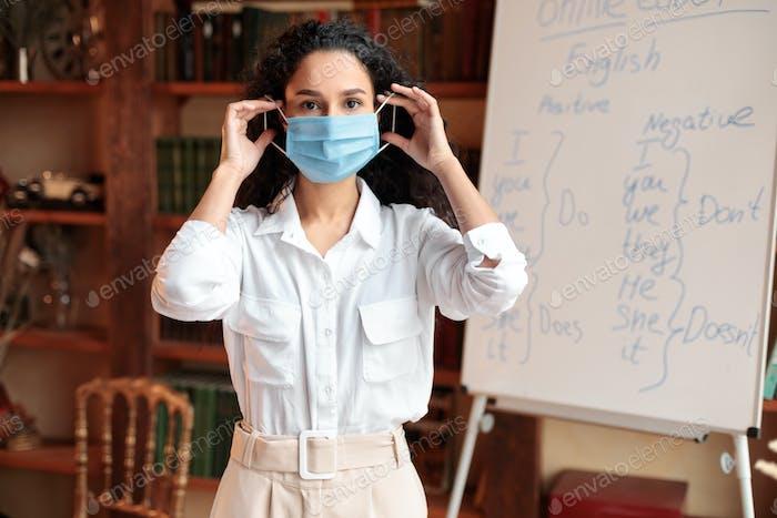 Учительница в маске для лица в классе